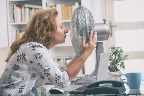 Menopausal woman holding fan